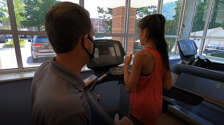 Staff member at Milford Fitness, wearing a mask and assisting a customer on the treadmill.